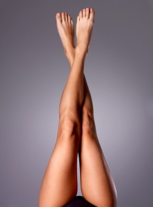 Beautiful female legs crossed in the air on a grey background